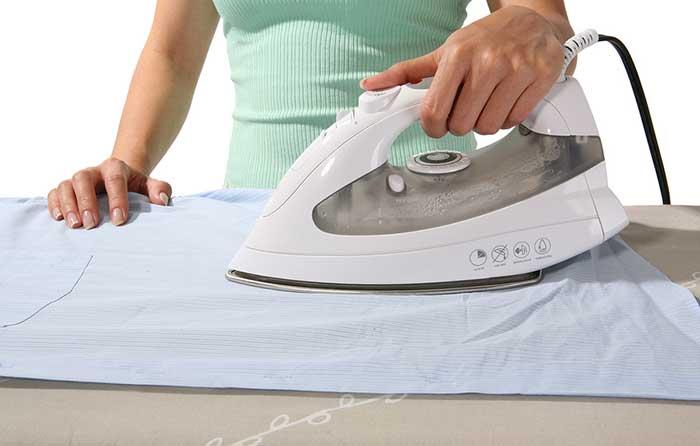 девушка гладит белье утюгом